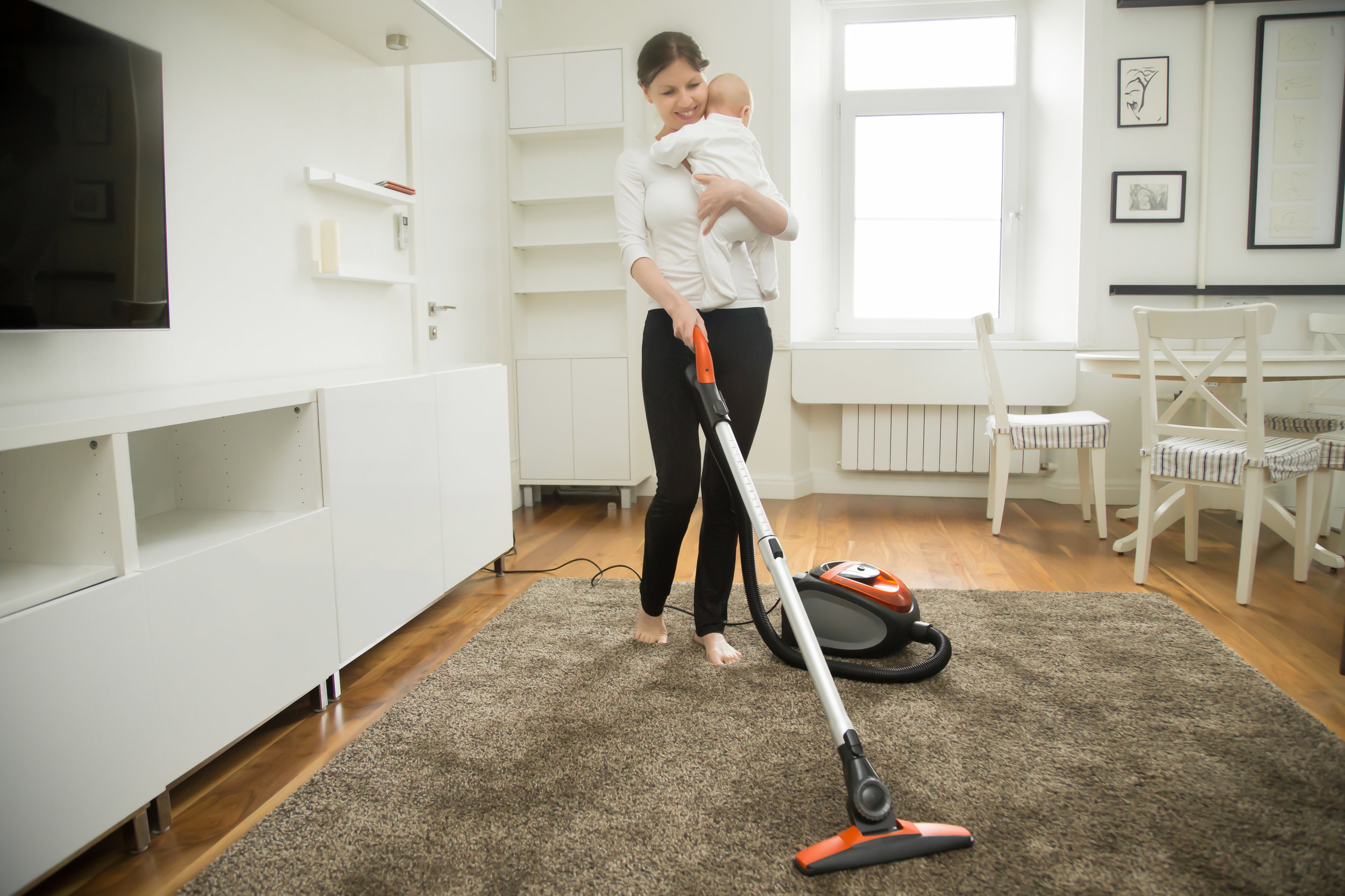 happy-smiling-woman-cleaning-the-carpet-holding-a-PGLLLMB.jpg