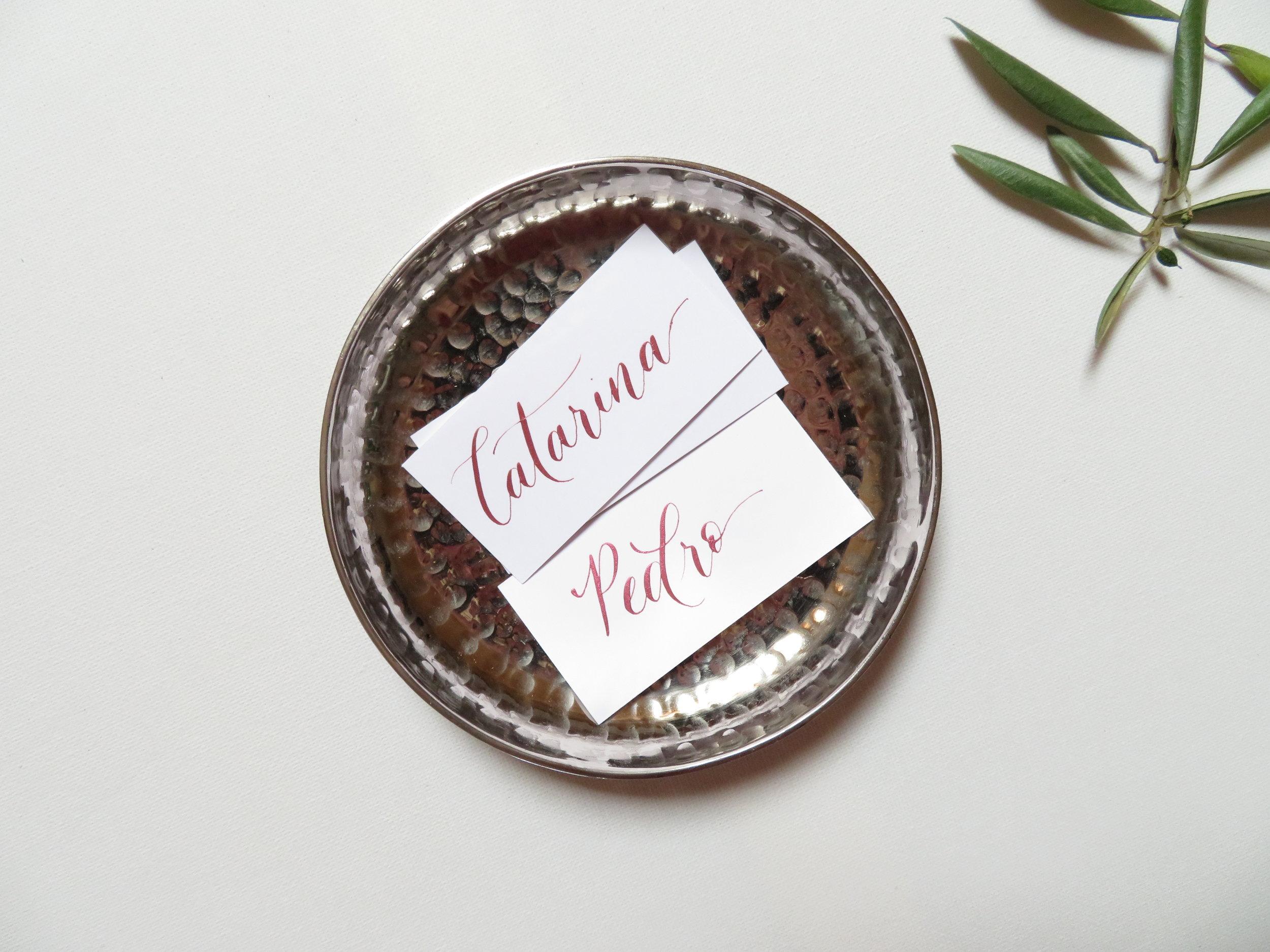 Marcadores de Mesa - Marcadores de mesa escritos em caligrafia moderna feita-à-mão a condizer com o design do teu convite.