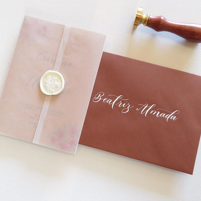 Wedding invitation wrapped in vellum paper with a wax seal to tie all together and some lovely calligraphy for the envelope 🧡