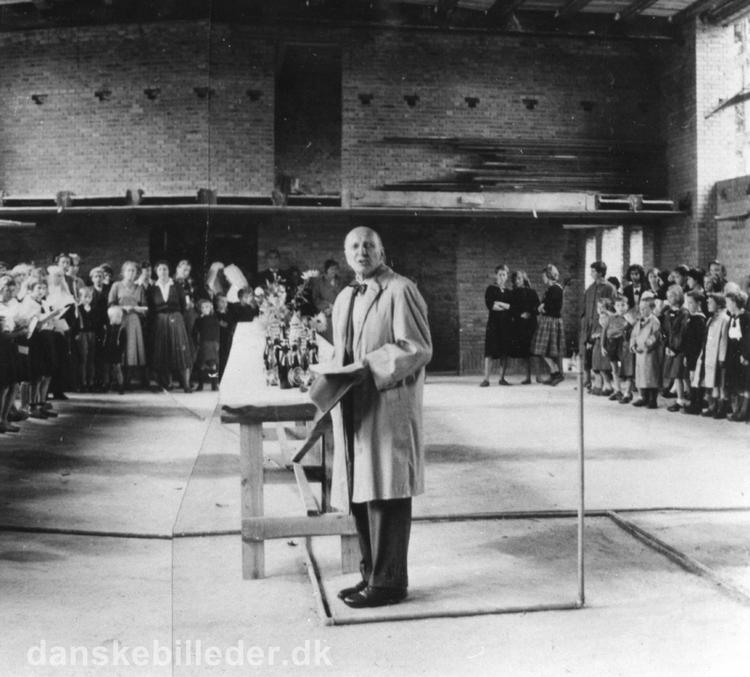 ARKITEKT ALFRED COCK-CLAUSEN HOLDER TALE I FESTSALEN PÅ RYGAARDS SKOLE VED REJSEGILDET FOR DEN NYE POLYGLOTAFDELING. FOTO TAGET DEN 16. SEPTEMBER 1958. KILDE: WWW.DANSKEBILLEDER.DK.