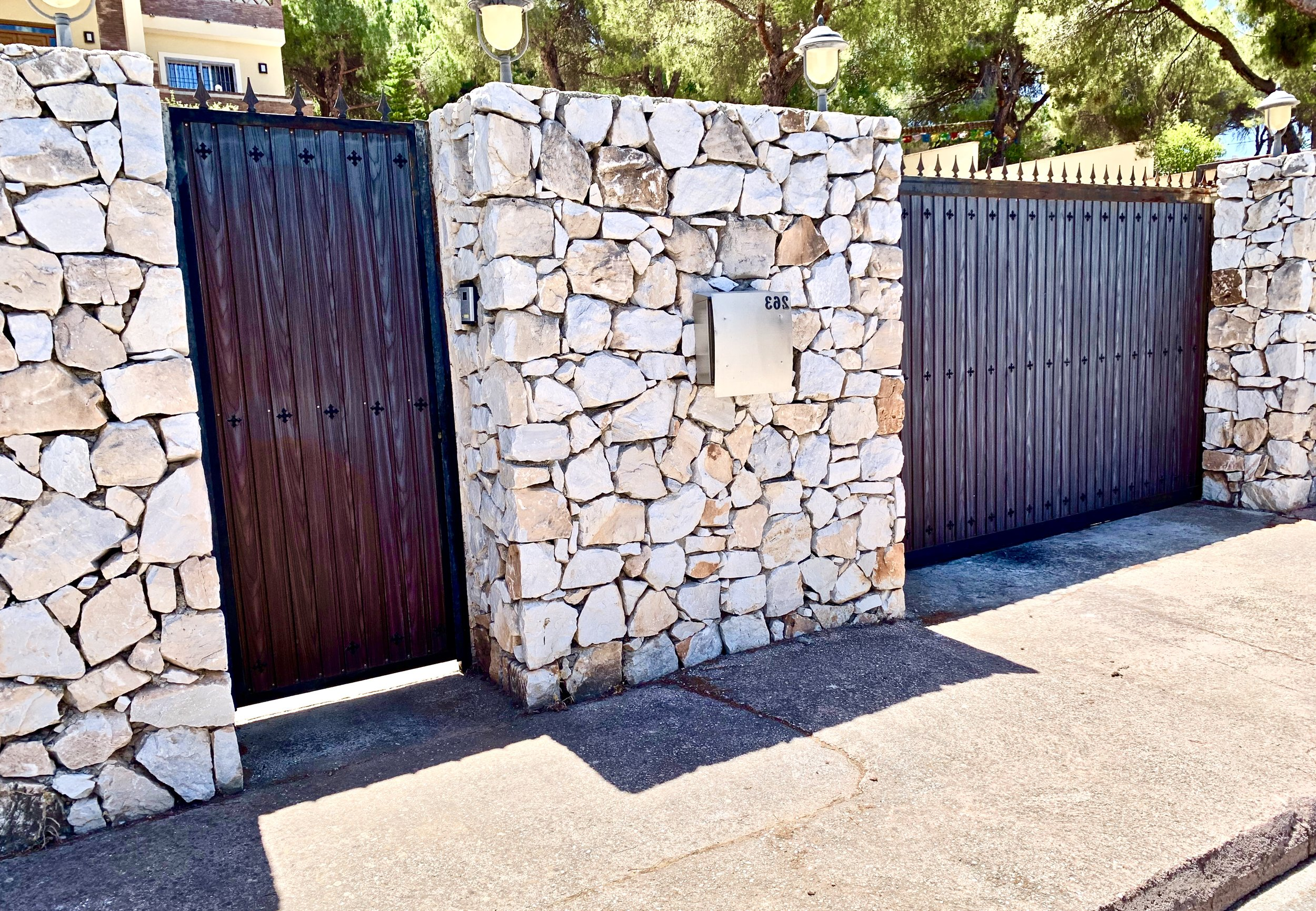 Sliding gate and door set in a stone wall, project built for the client in Alhaurin del Torre, Costa del Sol.