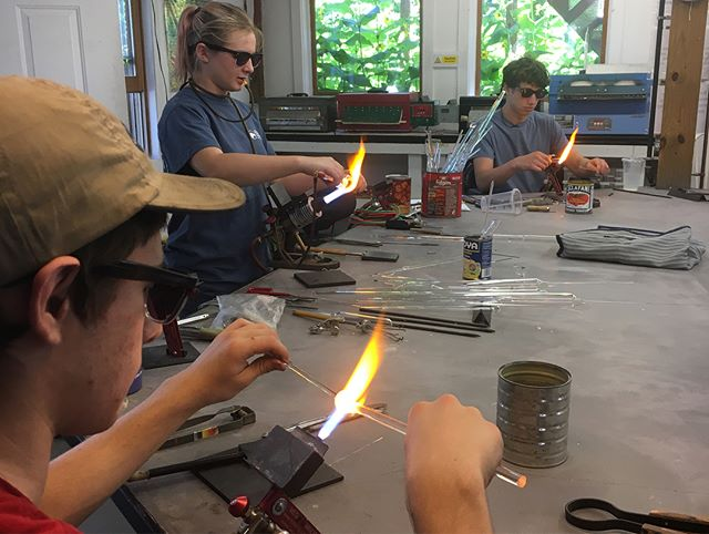 Week 2 is off to a great start here at @snowfarmcraft ! Me and @planemo_glass are Co-teaching a 2 week flameworking class for high schoolers and we are super impressed with their skill and ambition! The first picture is of our students working diligently, we even got one of our more experienced students to try out my Carlisle @carlislemachineworks ! The second photo is from last night after outrage ensued when @planemo_glass gave them the 10 minute warning before clean up 😂🙌🏻 it's awesome to see these kids get so stoked about their final projects! #stayglassy #learnup #artcamp #craftschool #snowfarm #lampwork