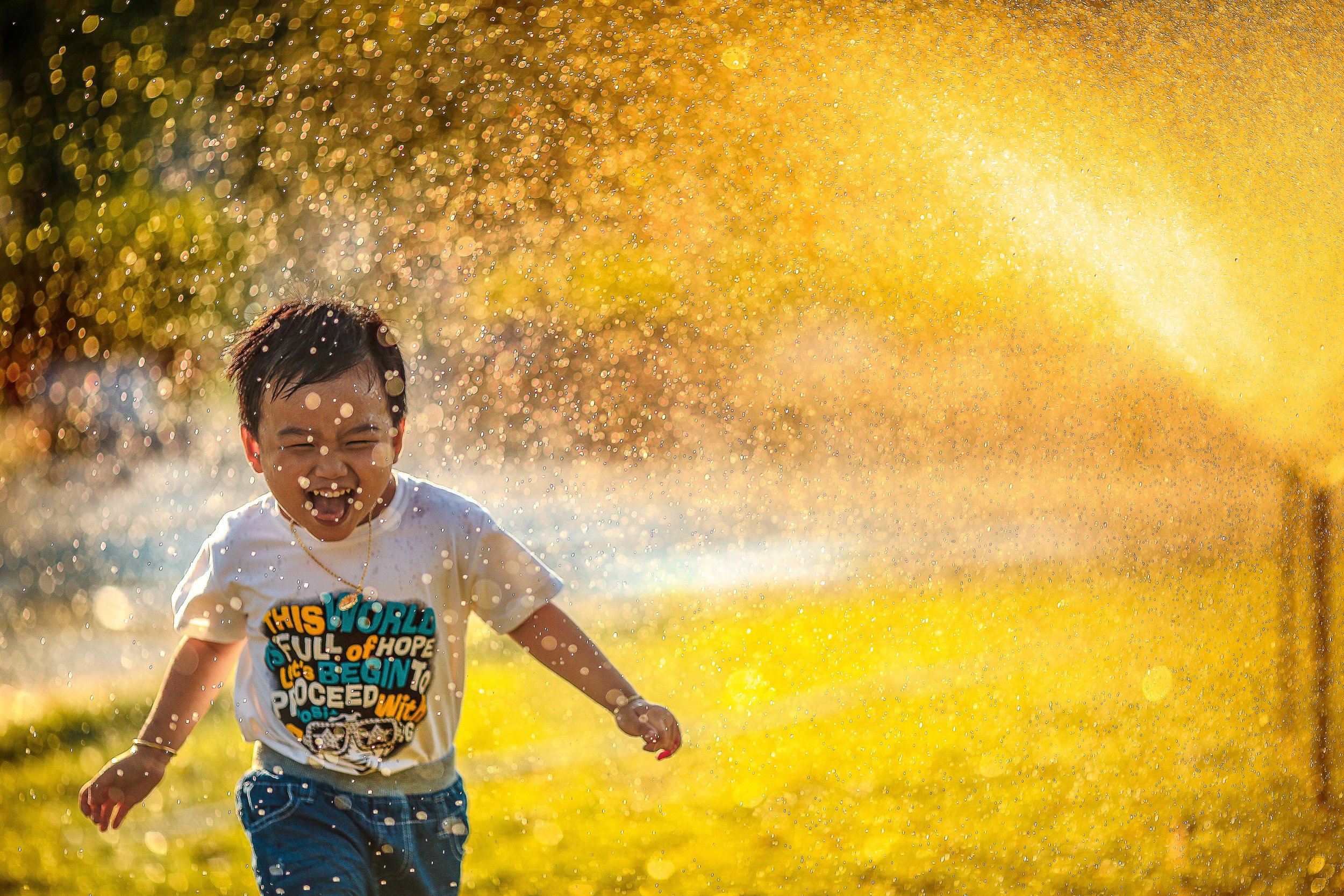 Child running and laughing through a sprinkler.