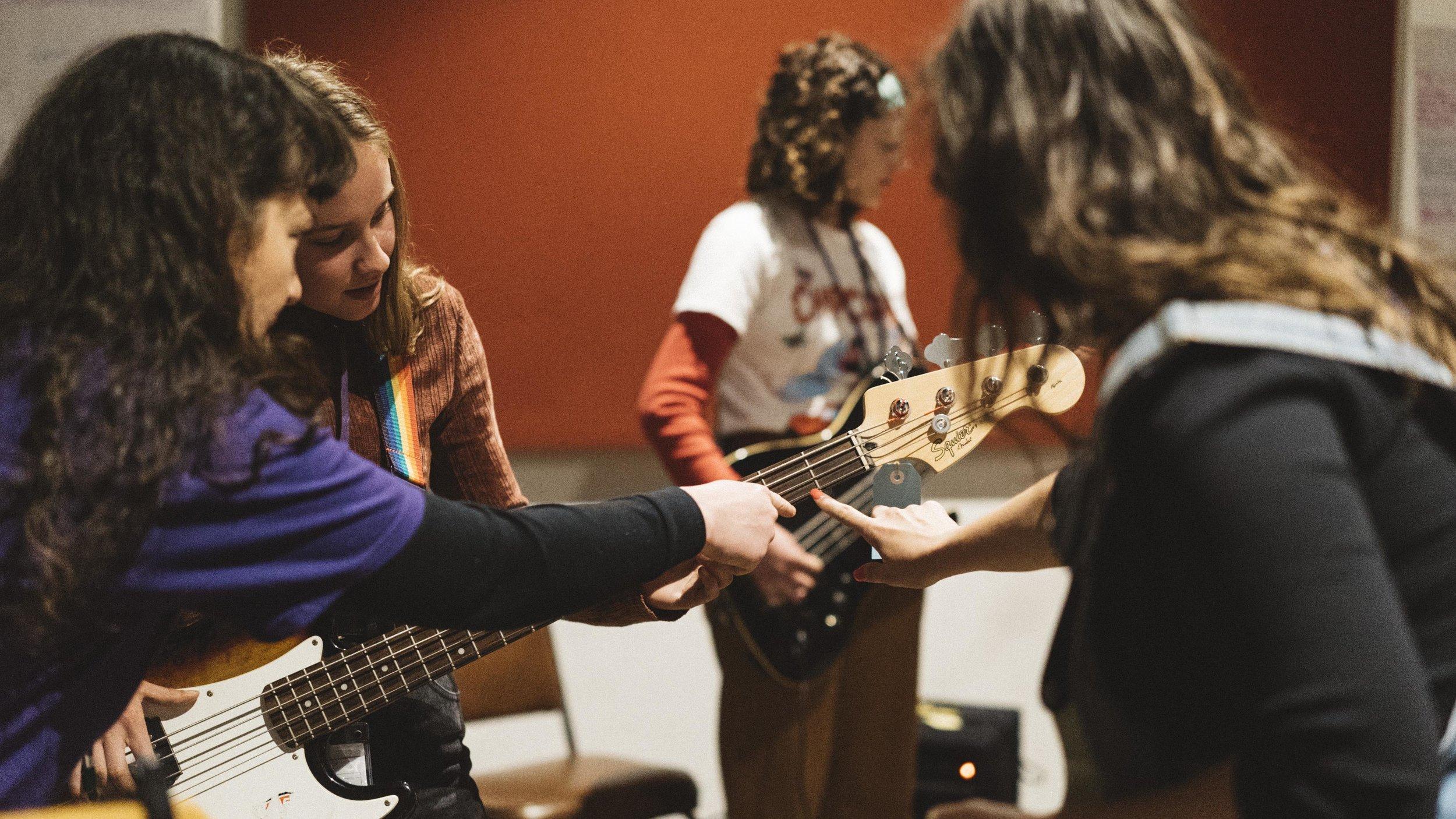 Photo: Girls Rock! Melbourne mentors Jade Stevens and Kelly-Dawn Hellmrich assisting a camper during bass instrument instruction. Photo credit: Sianne van Abkoude.