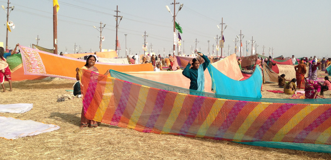 after a dip in the ganga, women dry their saris