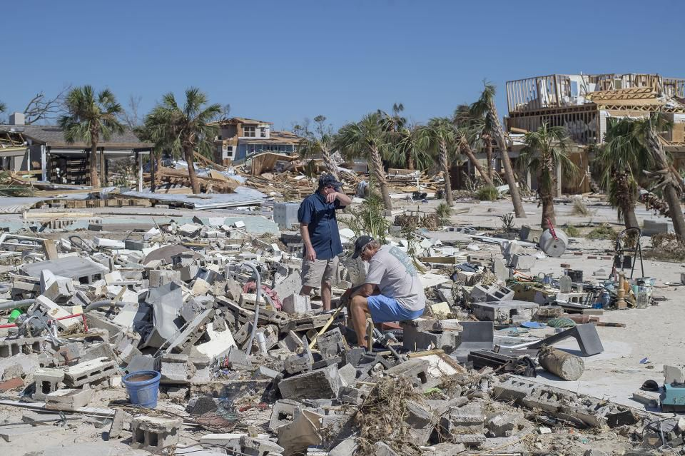 Residents survey debris after Hurricane Michael hit in Mexico Beach, Florida, U.S., on Friday, Oct. 12, 2018. Search-and-rescue teams found at least one body in Mexico Beach, the ground-zero town nearly obliterated by Hurricane Michael, an official said Friday as the scale of the storm's fury became ever clearer. Photographer: Zack Wittman/Bloomberg  © 2018 BLOOMBERG FINANCE LP