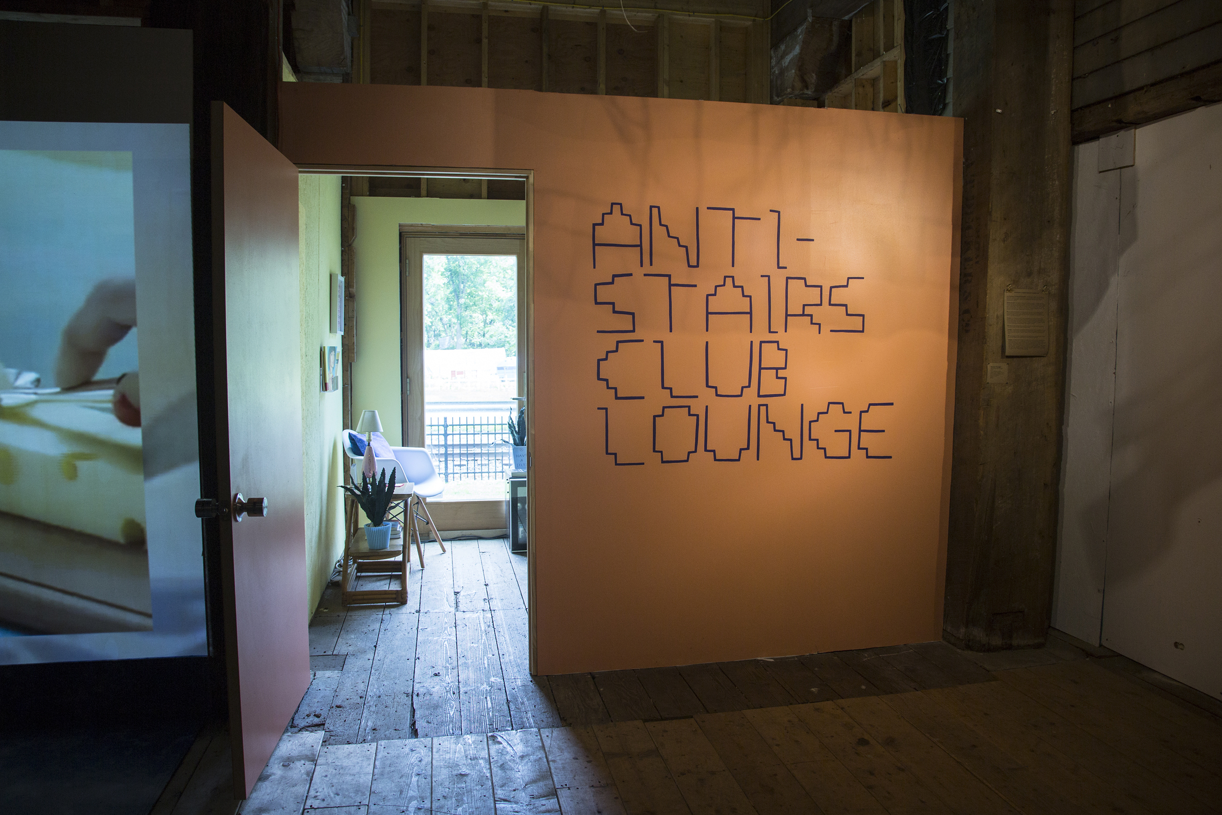 """An orange wall with big text in a stair-inspired font that says, """"Anti-Stairs Club Lounge."""""""