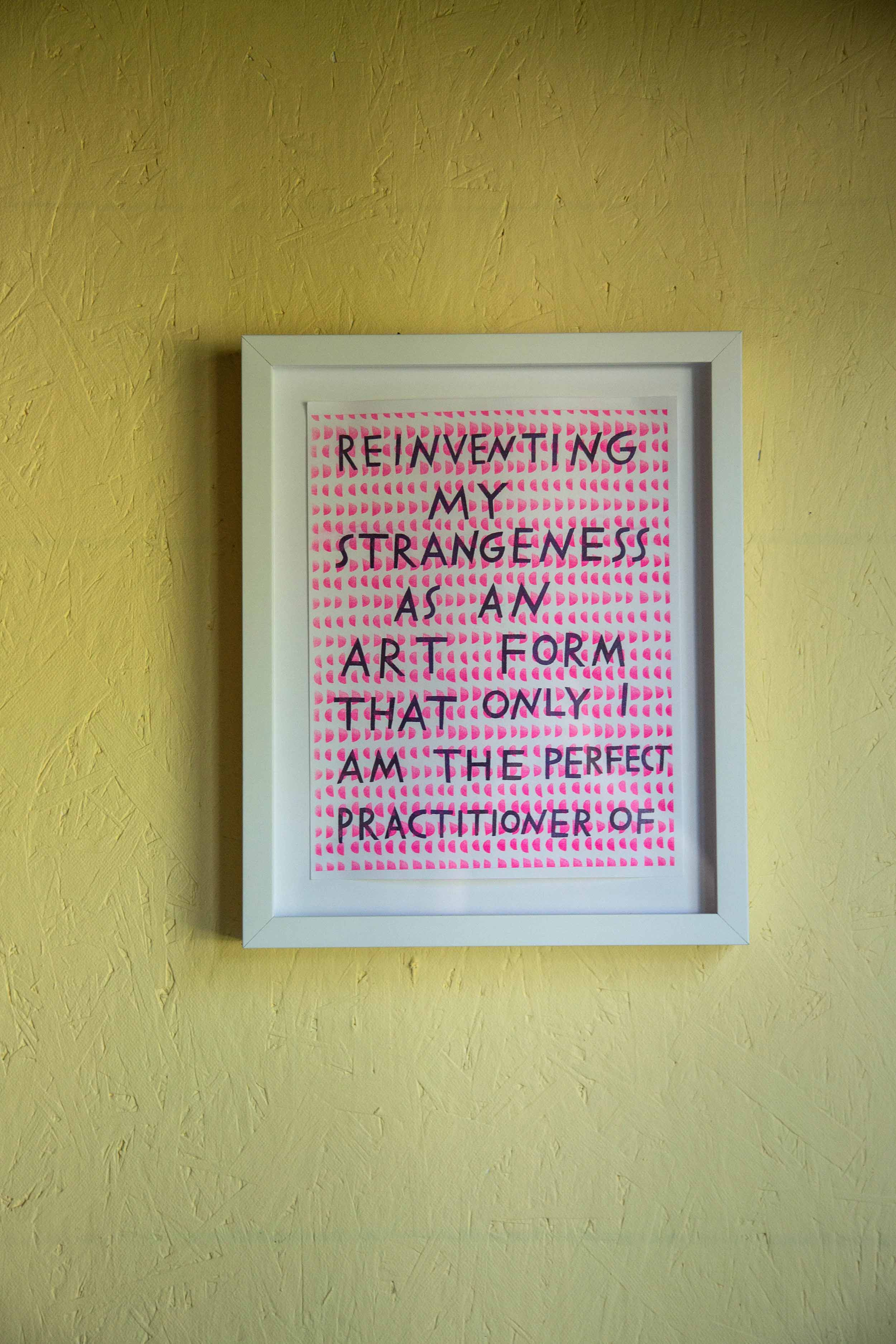 "A framed print reading, ""Reinventing my strangeness as an art form that only I am the perfect practitioner of."""