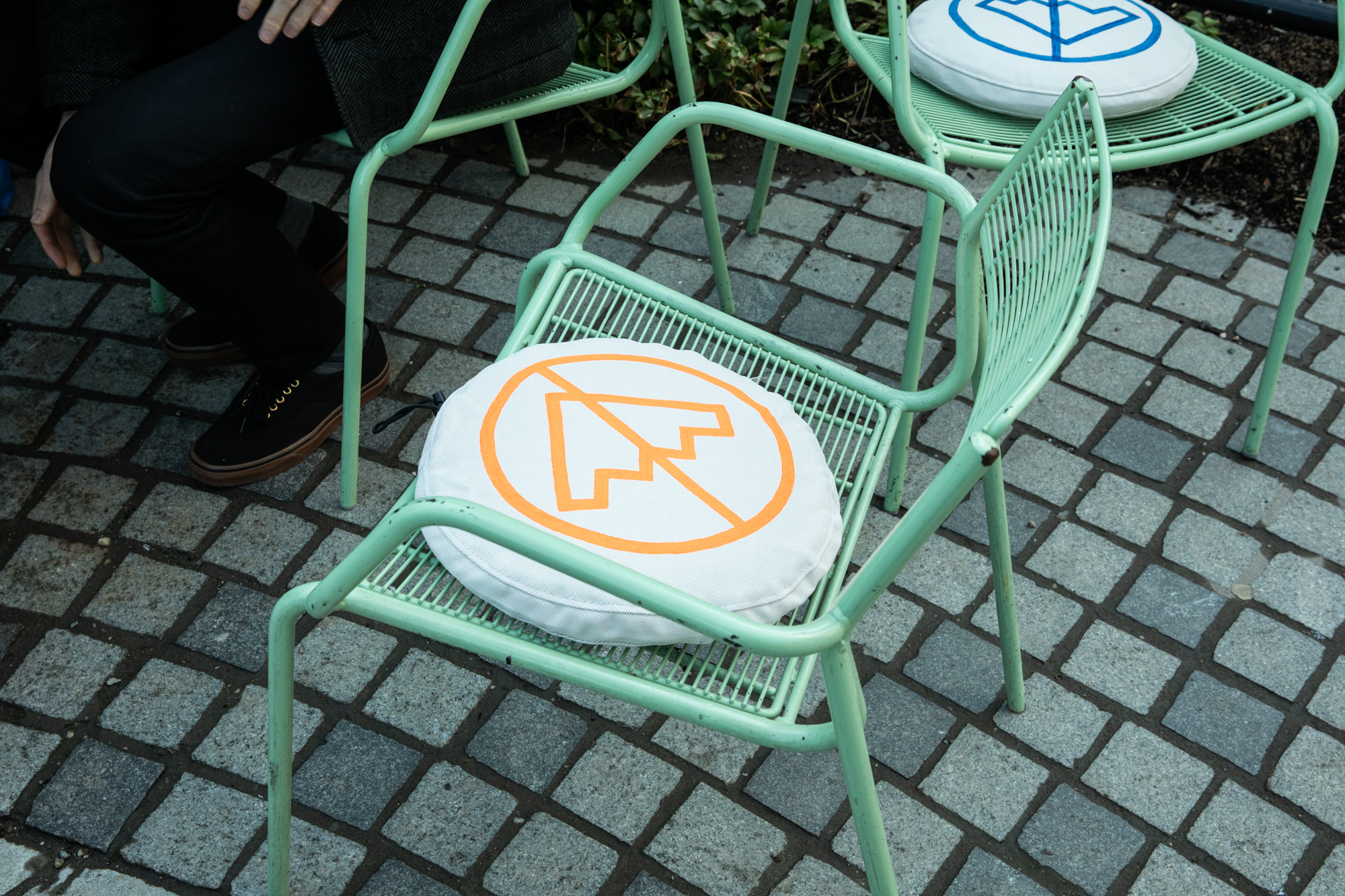 A green, metal chair with a round cushion painted with an orange crossed-out-stairs symbol.
