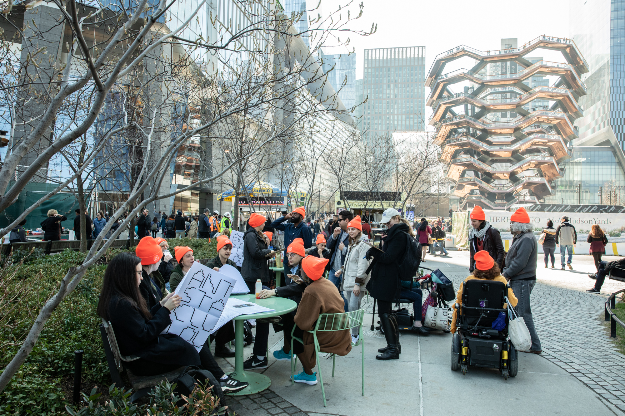 A group of about twenty people lounging in front of the Vessel. They are sitting, chatting, and reading. All wear neon orange Anti-Stairs Club Lounge beanies.