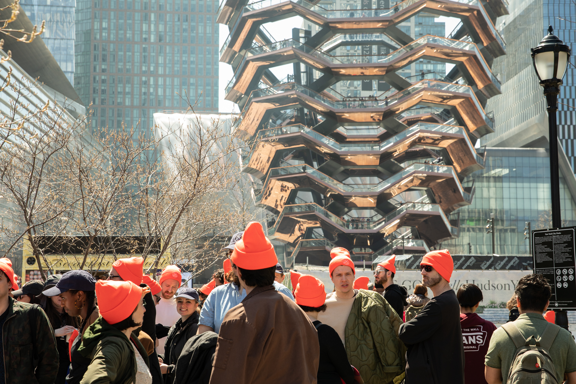 A sea of orange hats with the Vessel in the background.