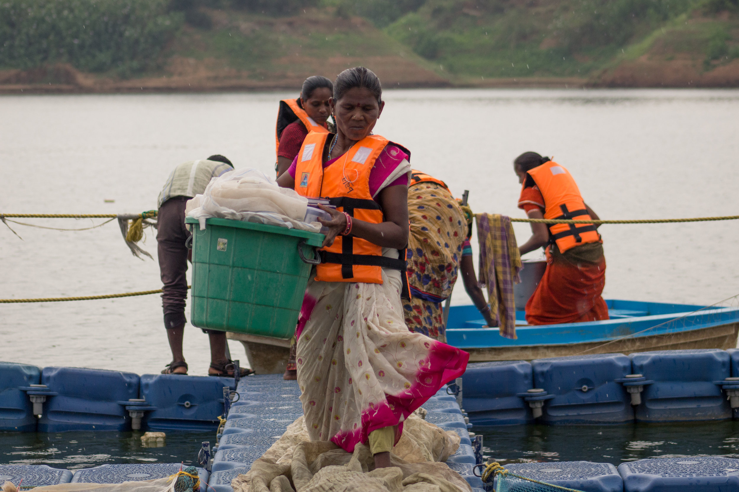 Local fishers carry the inputs required for the fisheries experiment.