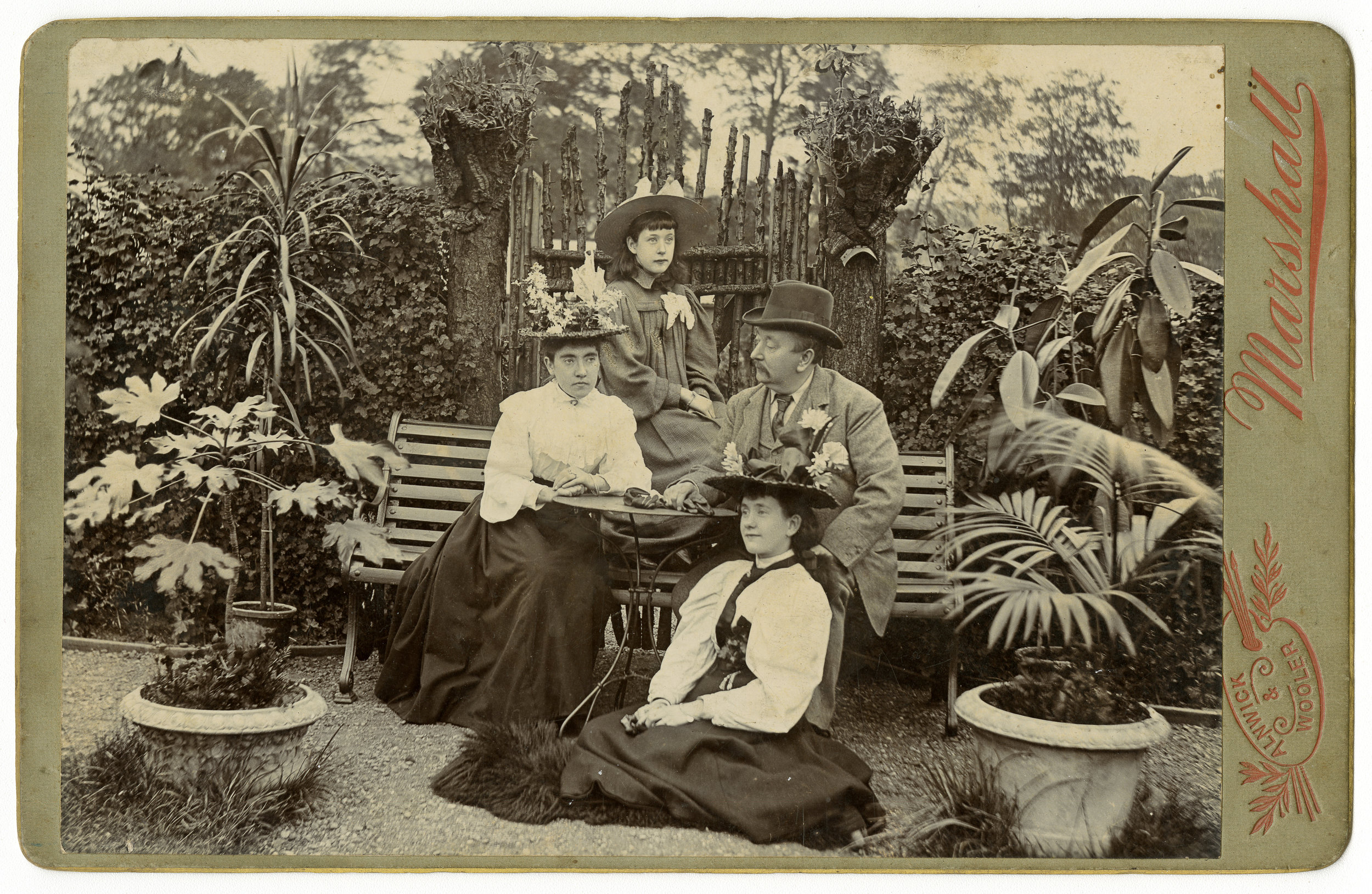 During the summer of 1897, a family pose together around a garden bench with extravagant floral hats and potted palms.