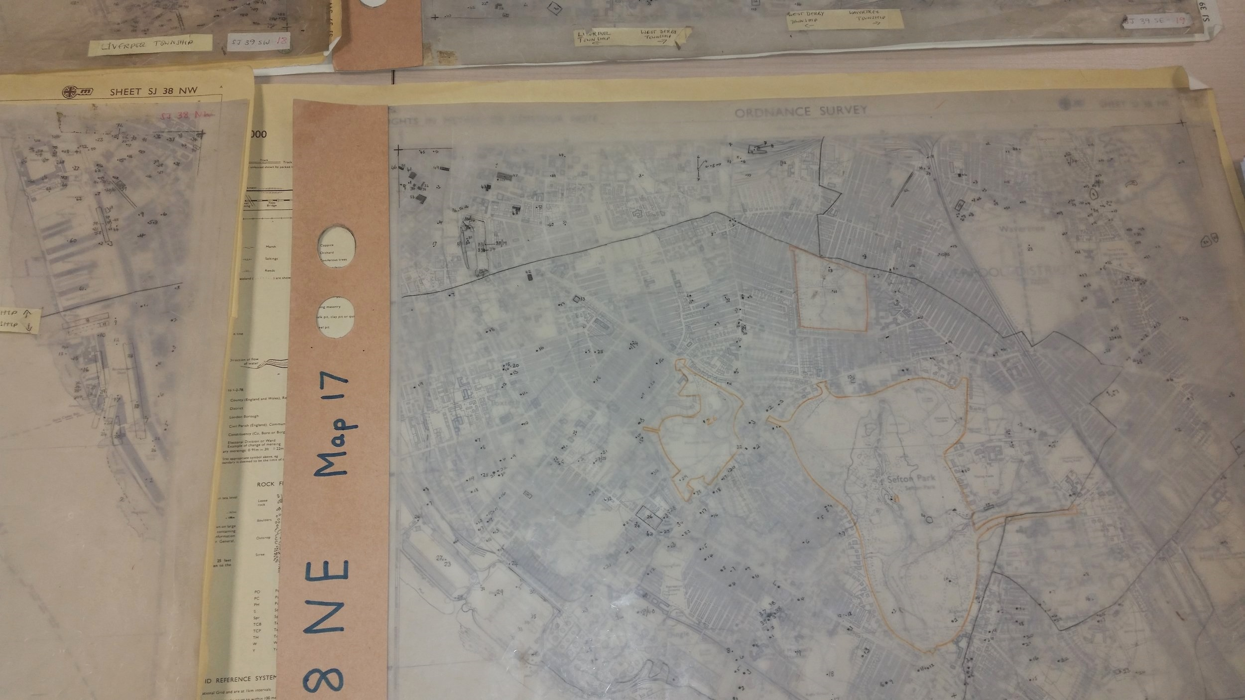 Tracing paper with notes in pencil covering the map, showing spots where we have information about that building or piece of land.
