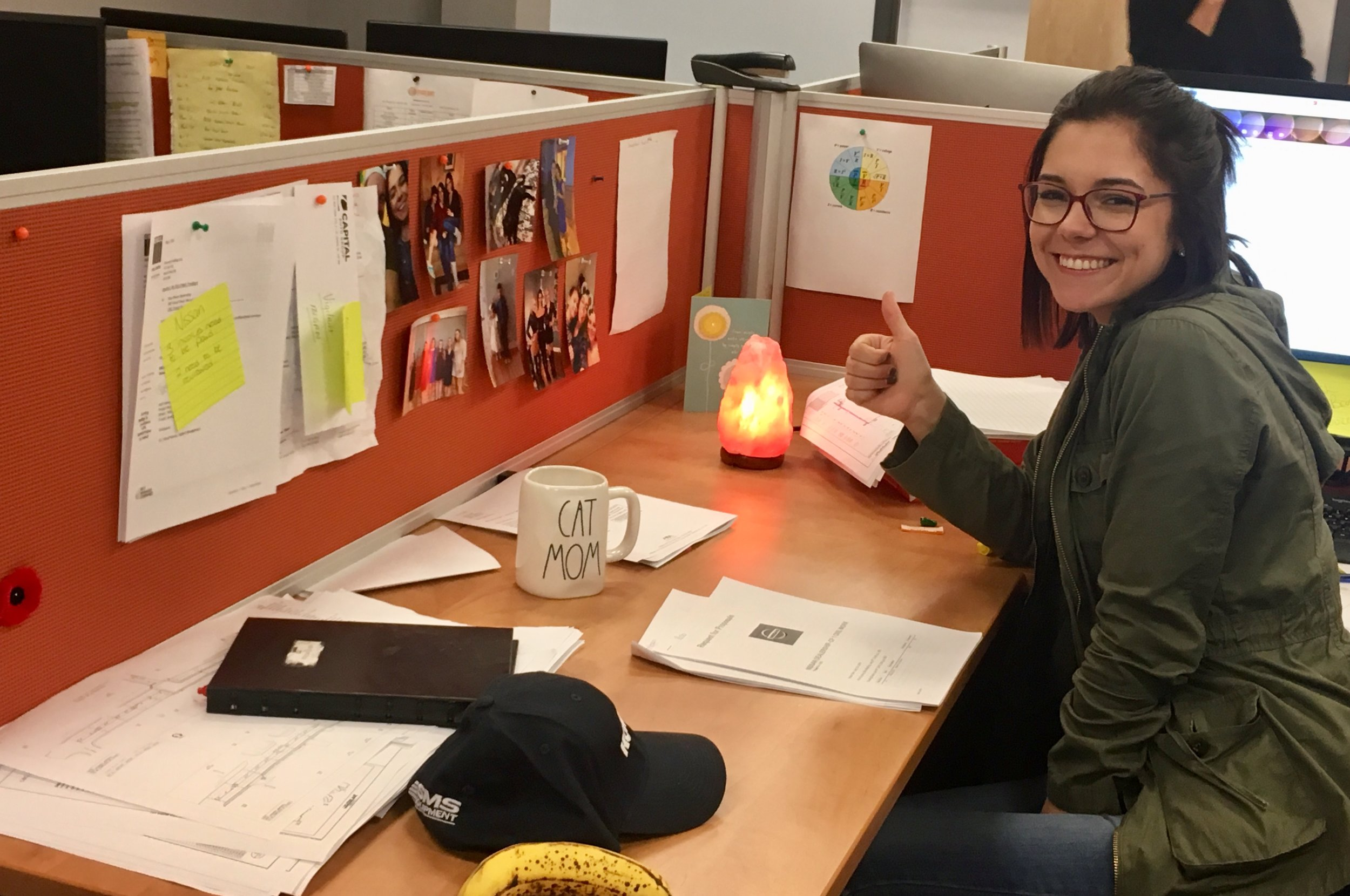 Megan with her Salt lamp, CAT MOM mug and photos on her cubical