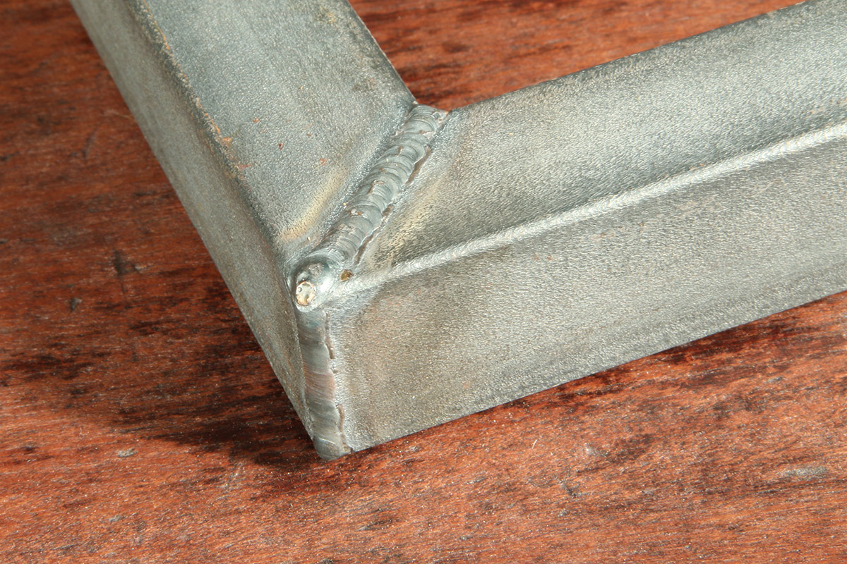 Exposed butt and fillet weld (flat surface and corner joint) for distinctive aesthetics. The frame features advanced degree of oxidation.