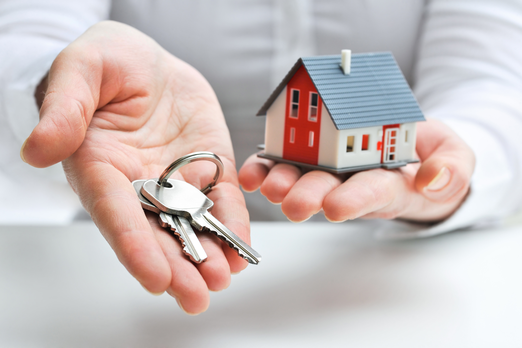 Person holding a house and keys.jpg