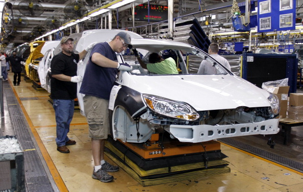Workers build a Ford Focus on the assembly line at the Ford Motor Co.'s Michigan Assembly Plant December 14, 2011 in Wayne, Michigan. (Photo by Bill Pugliano/Getty Images)