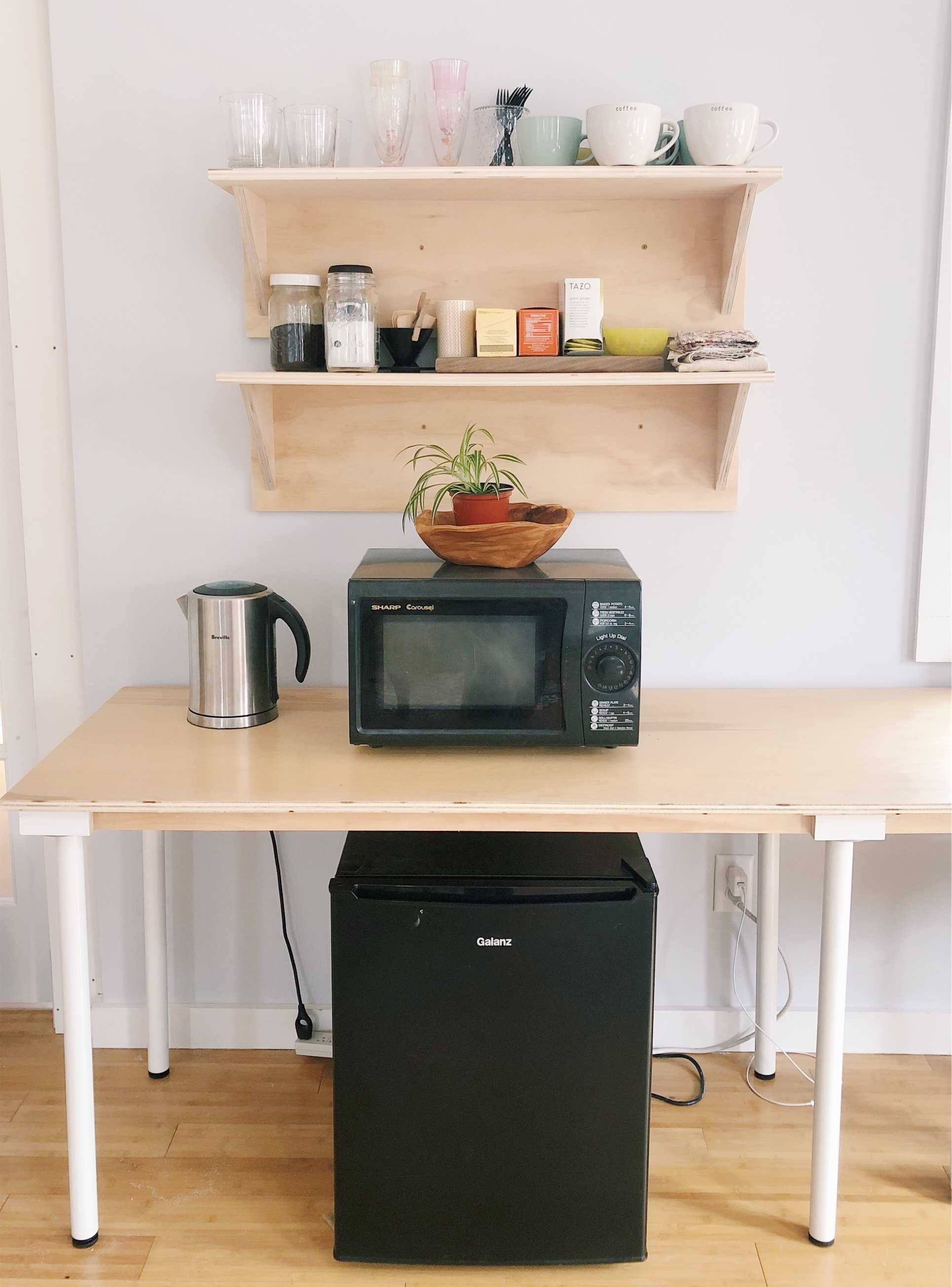 Kitchenette with electric kettle and mini-fridge.