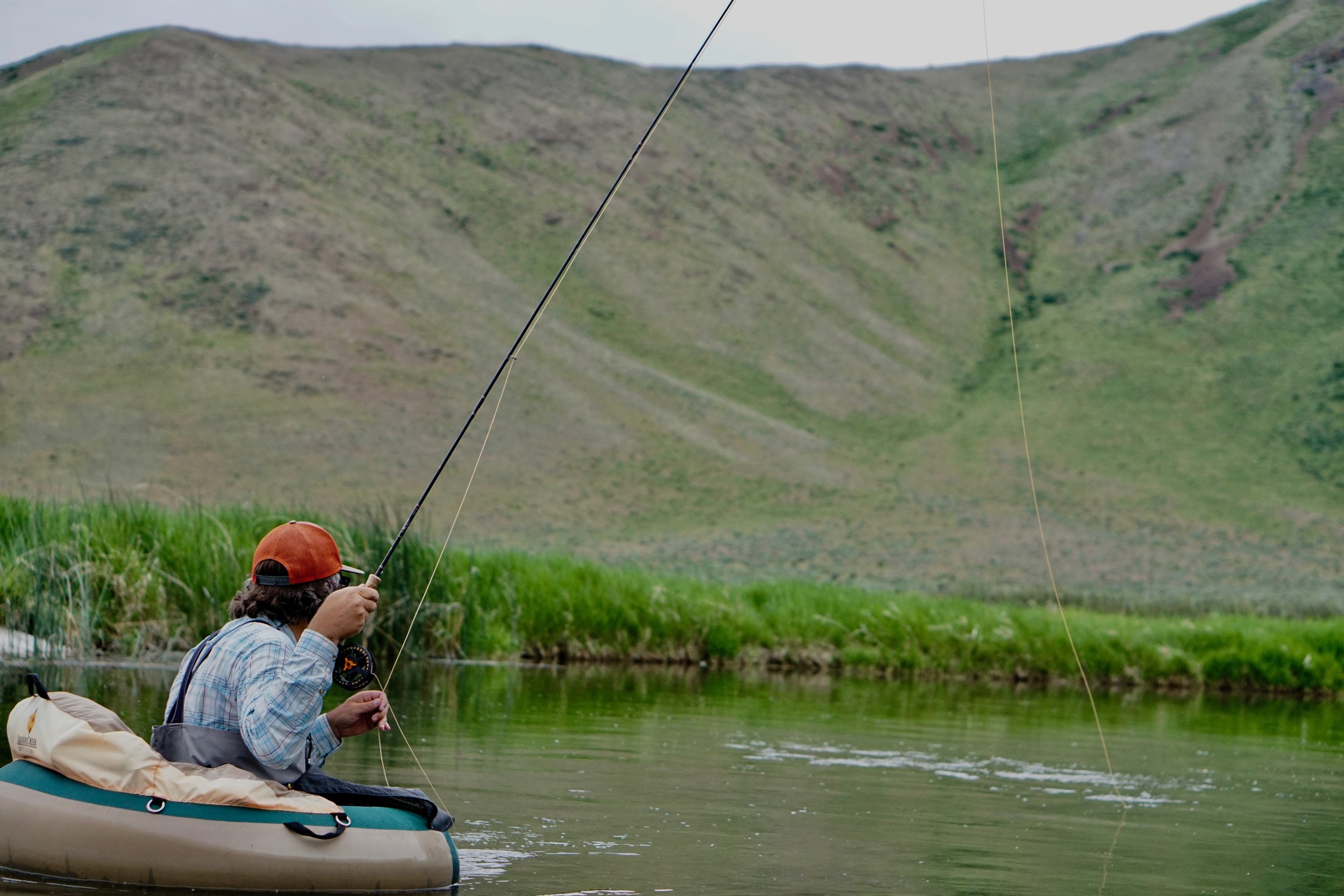 Silver Creek Outfitter's Guide Taite Pearson Pulls back the tip to tighten the rig before lowering the rod tip to drift to a rising fish.