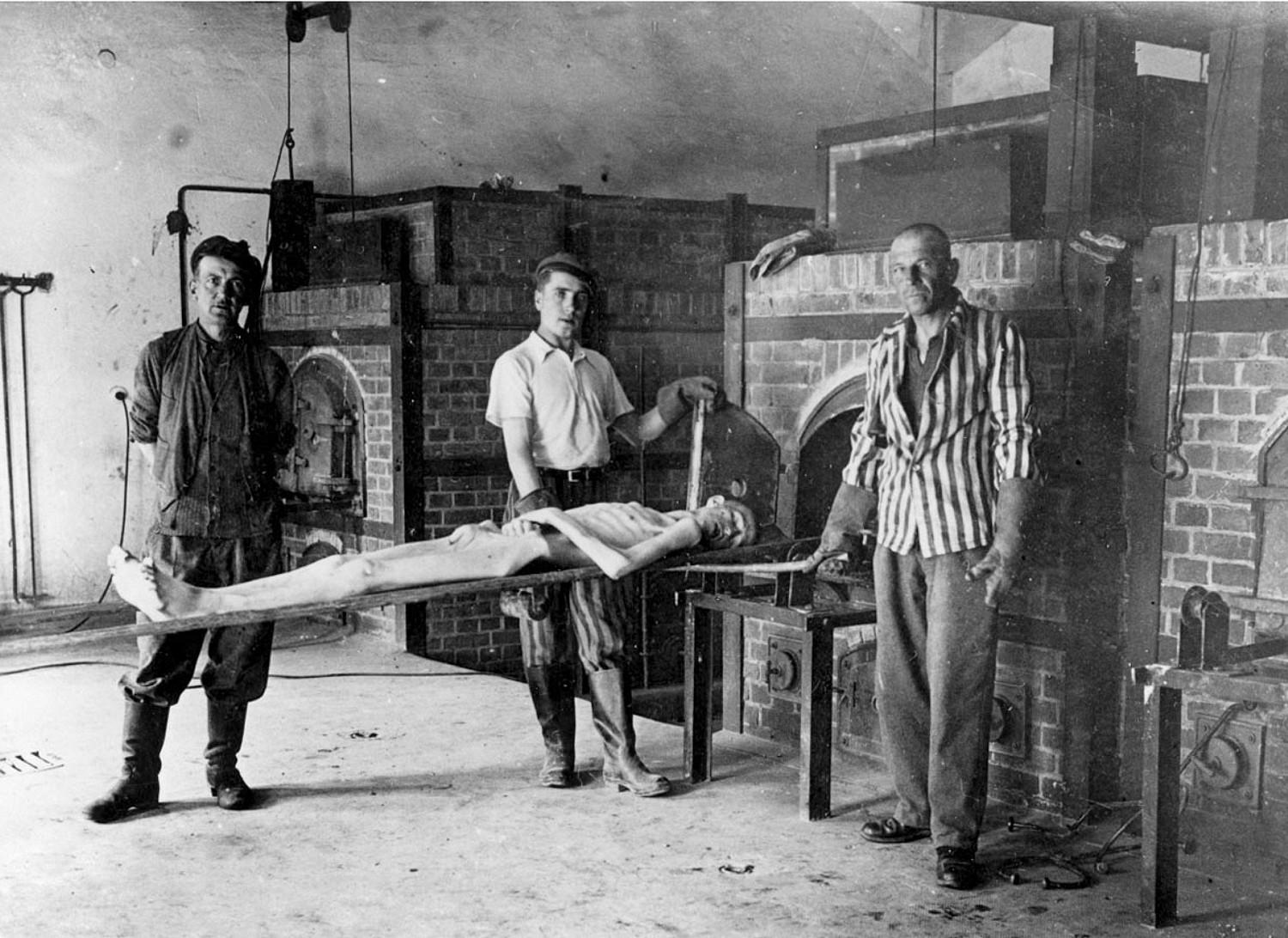 [Survivors of the Dachau concentration camp demonstrate the operation of the crematorium by pushing a corpse into one of the ovens. Dachau, Germany, April 29-May 10, 1945.]