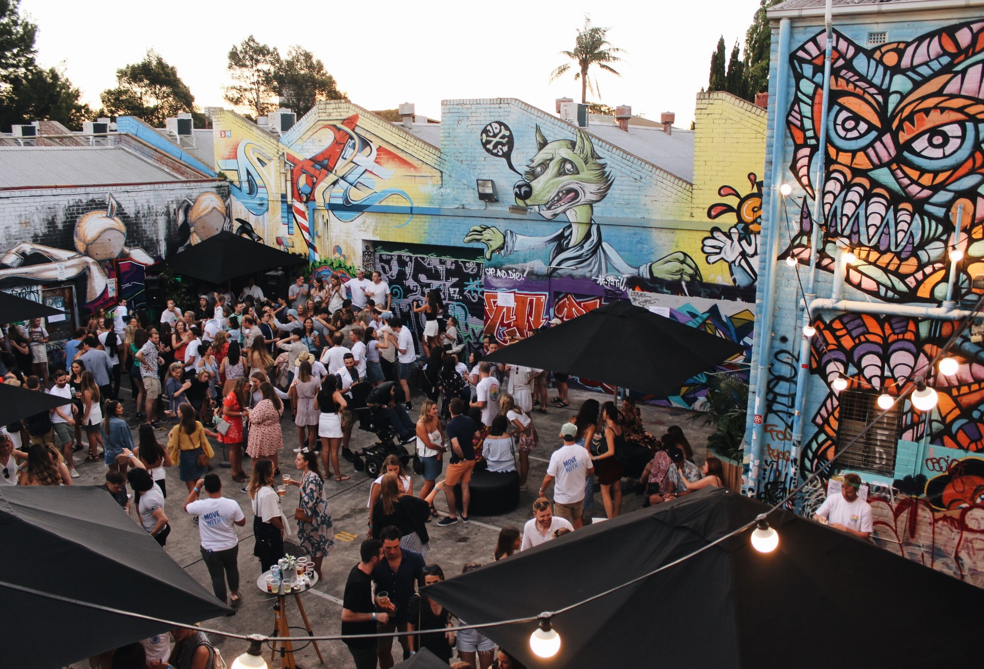 An aerial image of an outdoor party in a laneway with street art and fairy lights