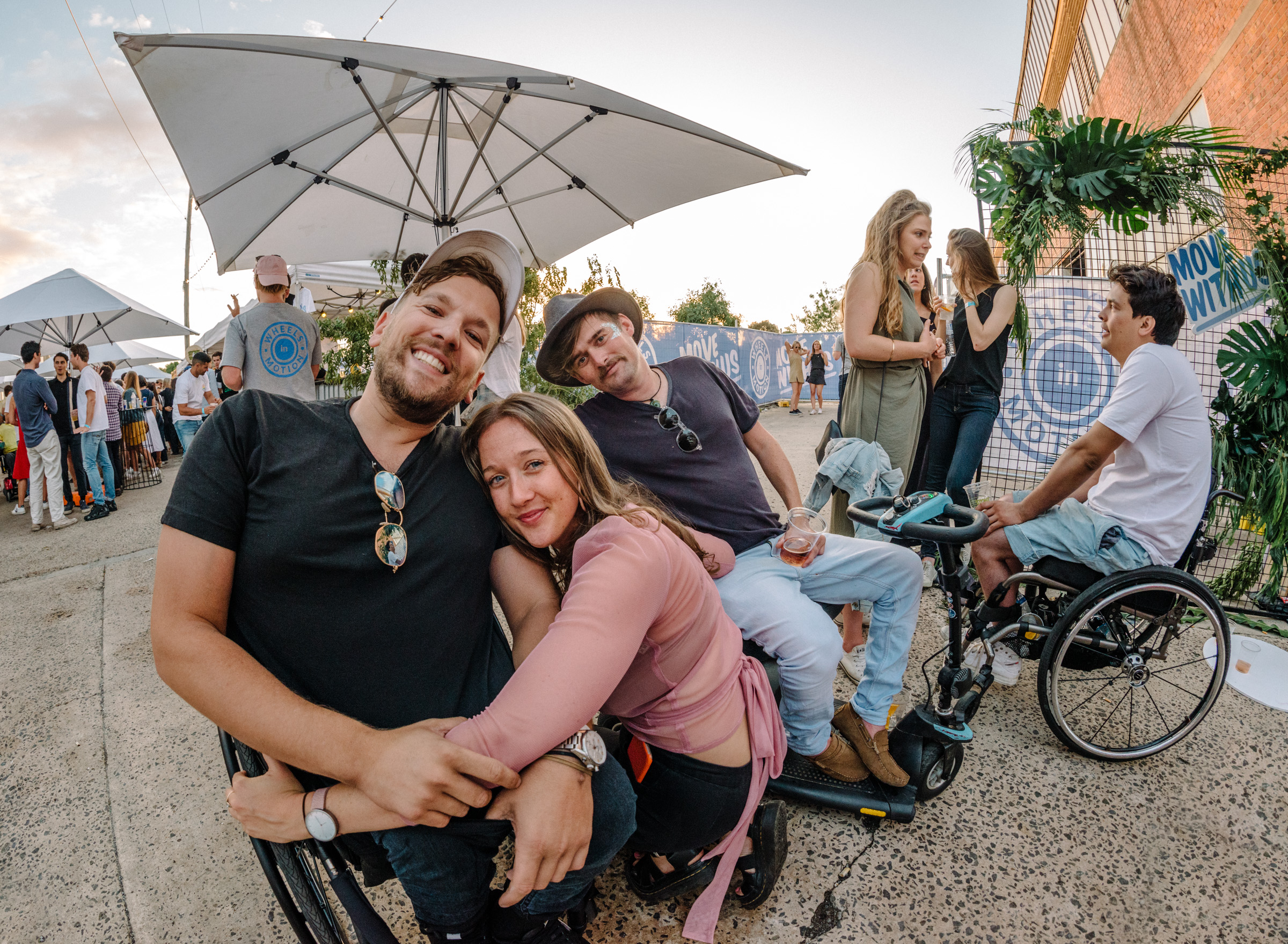 Image of 3 friends hugging. One uses a wheelchair, one uses a mobility scooter and one is squatting. There is another wheelchair user in the background. Everyone looks cool and happy!