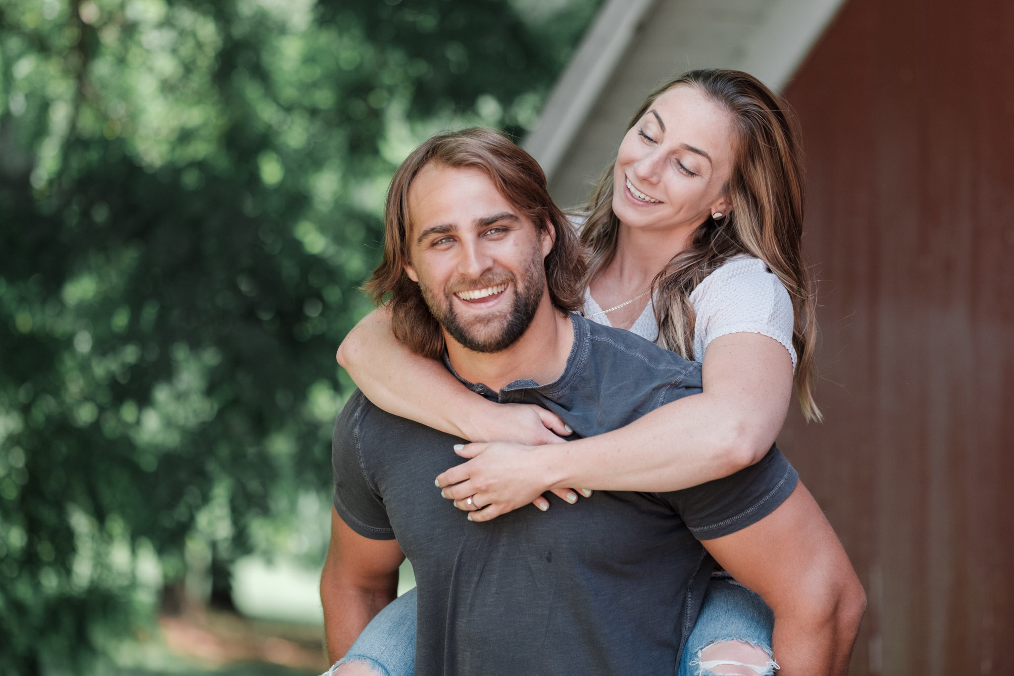 Crossfit couple embrace at The Pavilion at Orchard Ridge Farms during an engagement session next to red barn.