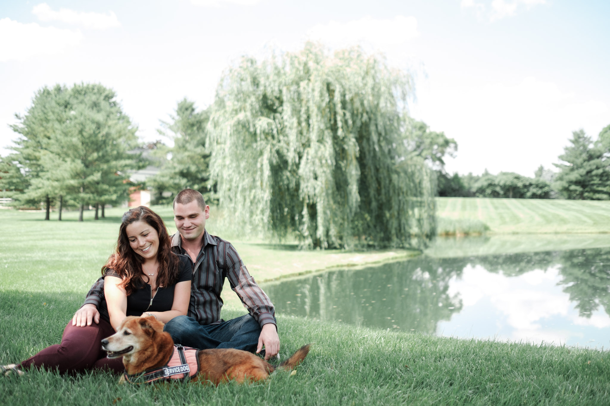 Couple sits with their dog during engagement session at The Pavilion at Orchard Ridge Farms in front of pond with willow tree behind them.