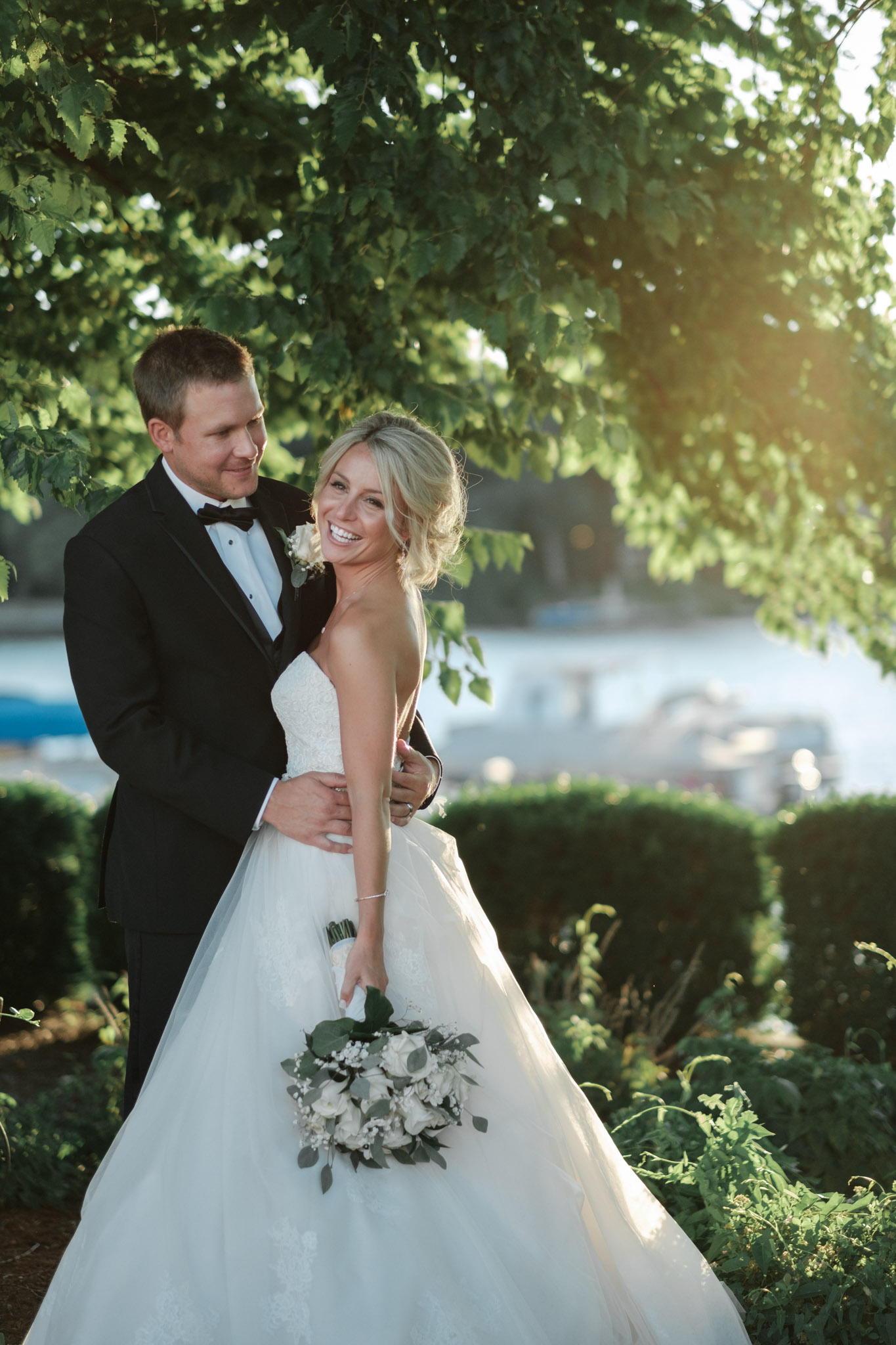 Bride and Groom smiling and embracing during golden hour overlooking river in rockford illinois standing on the dock at prairie street brewhouse