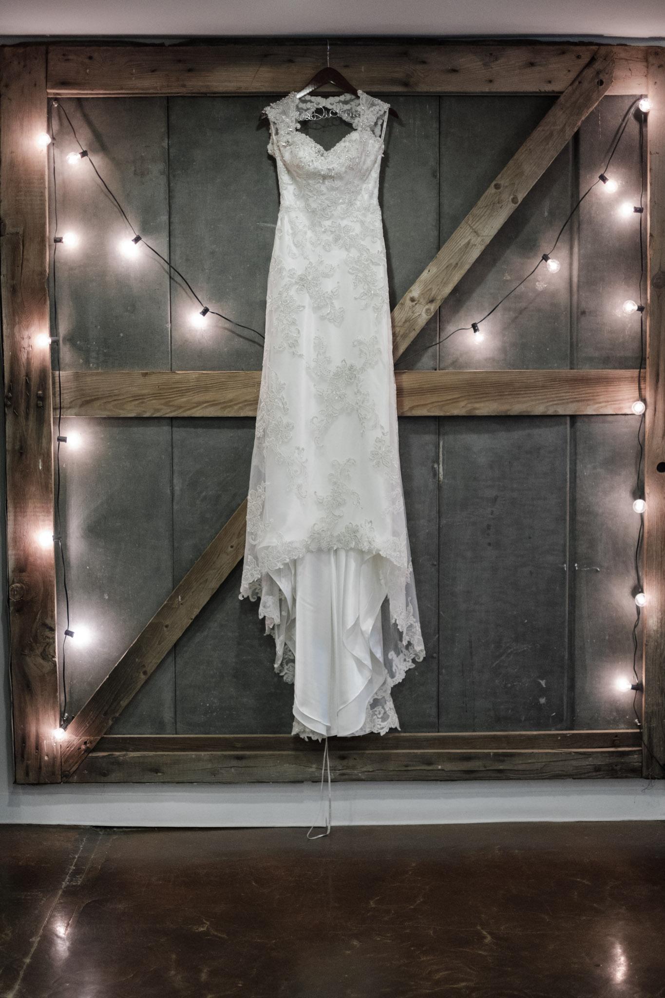 bride dress hanging on barn door with market lights surrounding it