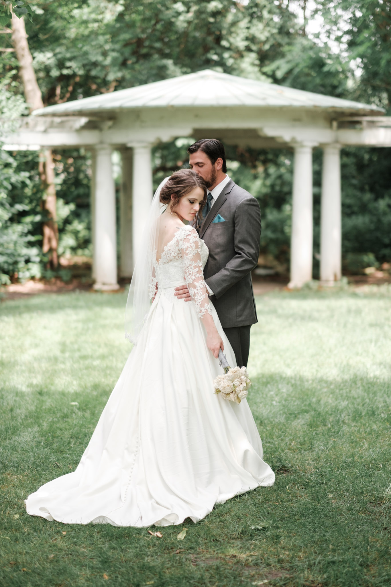 Bride and groom embrace in front of pergola at Sinnissippi Gardens in Rockford, Illinois during their first look.