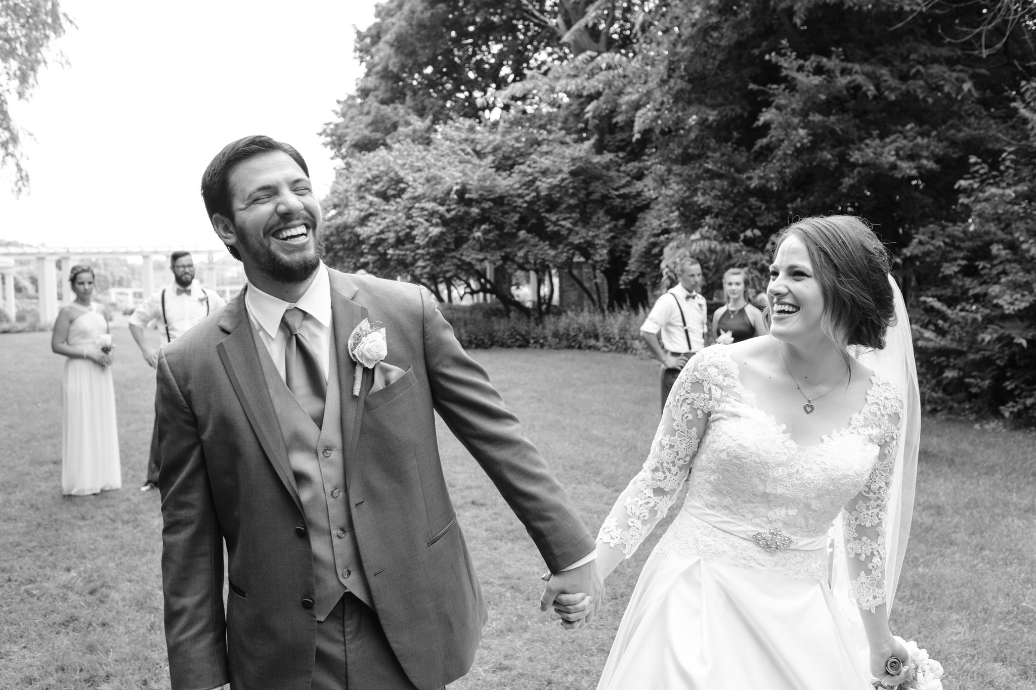 Black and white of bride and groom holding hands while laughing and walking at Sinnissippi Gardens in Rockford Illinois.