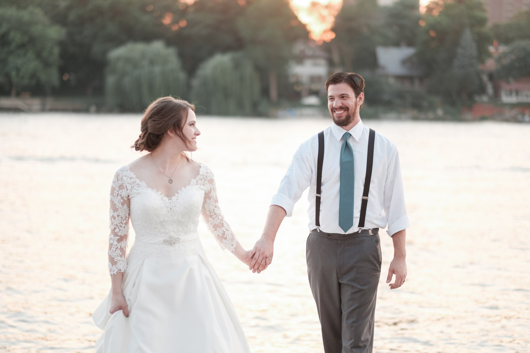 Bridal portrait during golden hour sunset on the dock with river in the background as couple looks at eachother walking holding hands and smiling.