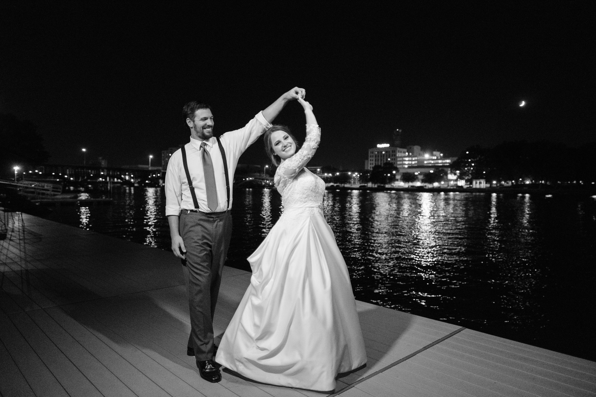 bride and groom dancing on the dock at prairie street brewhouse after dark.