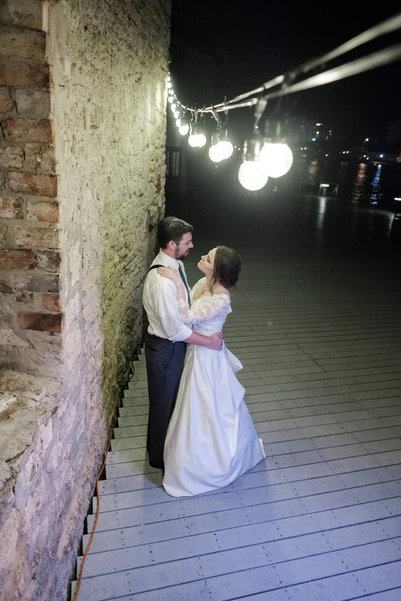Bride and groom portrait under market lights on the dock with limestone wall behind groom at Prairie Street Brewhouse in Rockford, Illinois.
