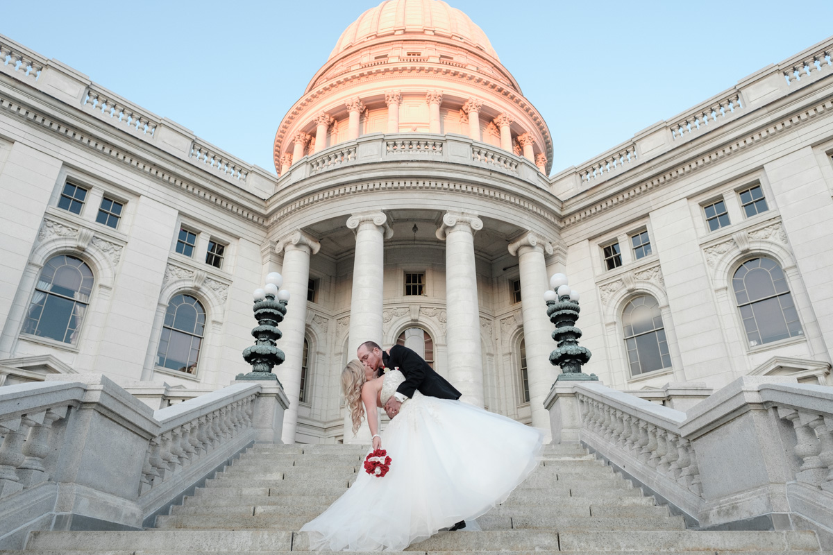 Groom dipping and kissing bride on the steps of the Capital Building in downtown Madison, Wisconsin.