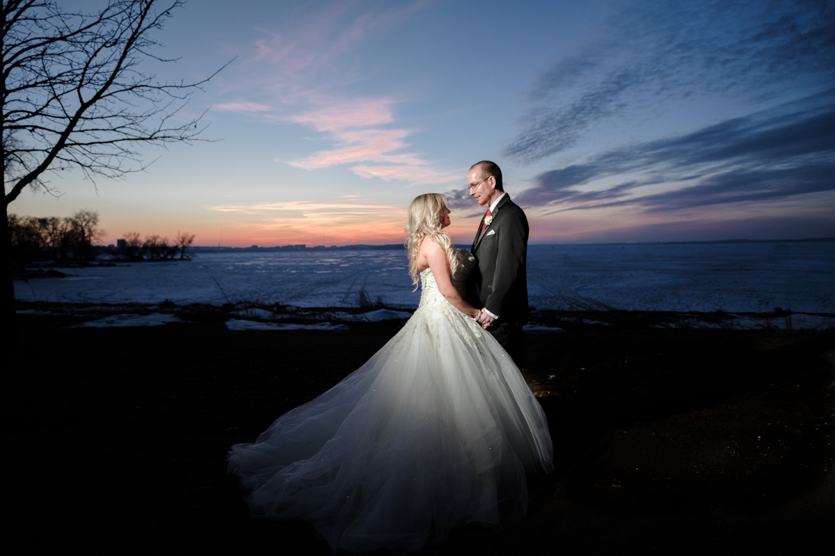 Bride and groom kissing as sunsets behind them with frozen lake in downtown Madison, Wisconsin.