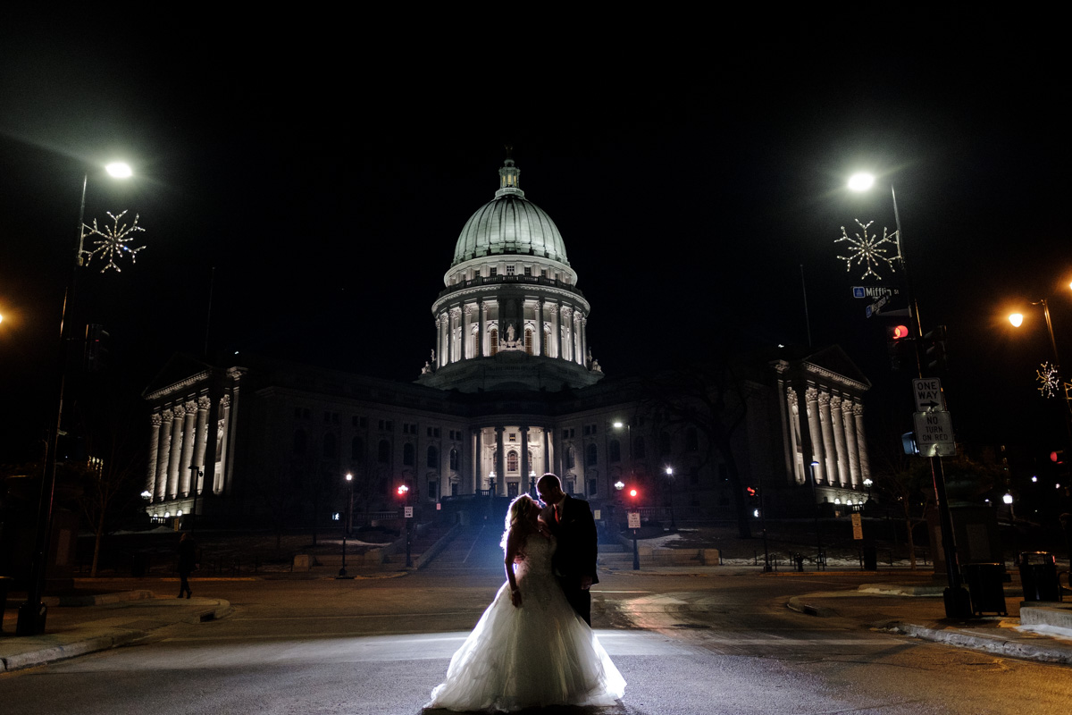 Wisconsin Capitol Building in downtown Madison, Wisconsin lit up in lights with couple backlit kissing in the road.
