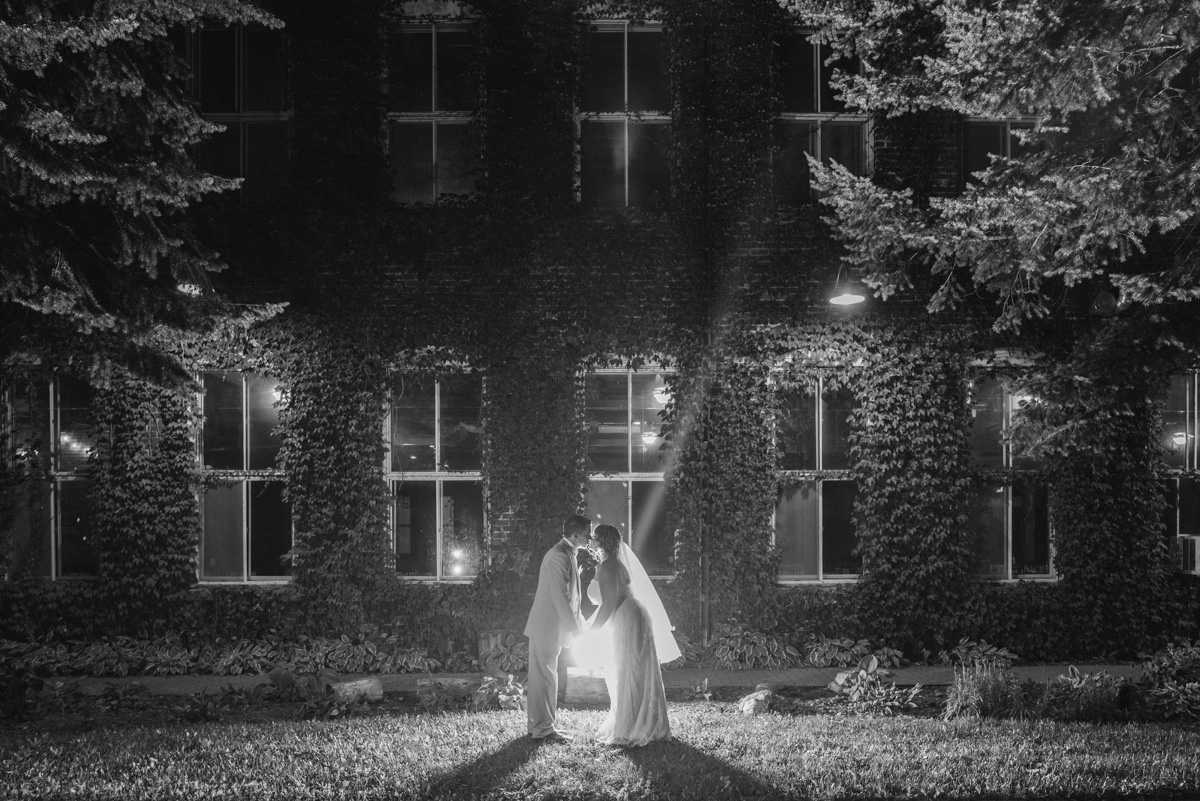 black and white photo of bride and groom kissing with backlighting of ivy and brick on starline factory wedding venue harvard, illinois