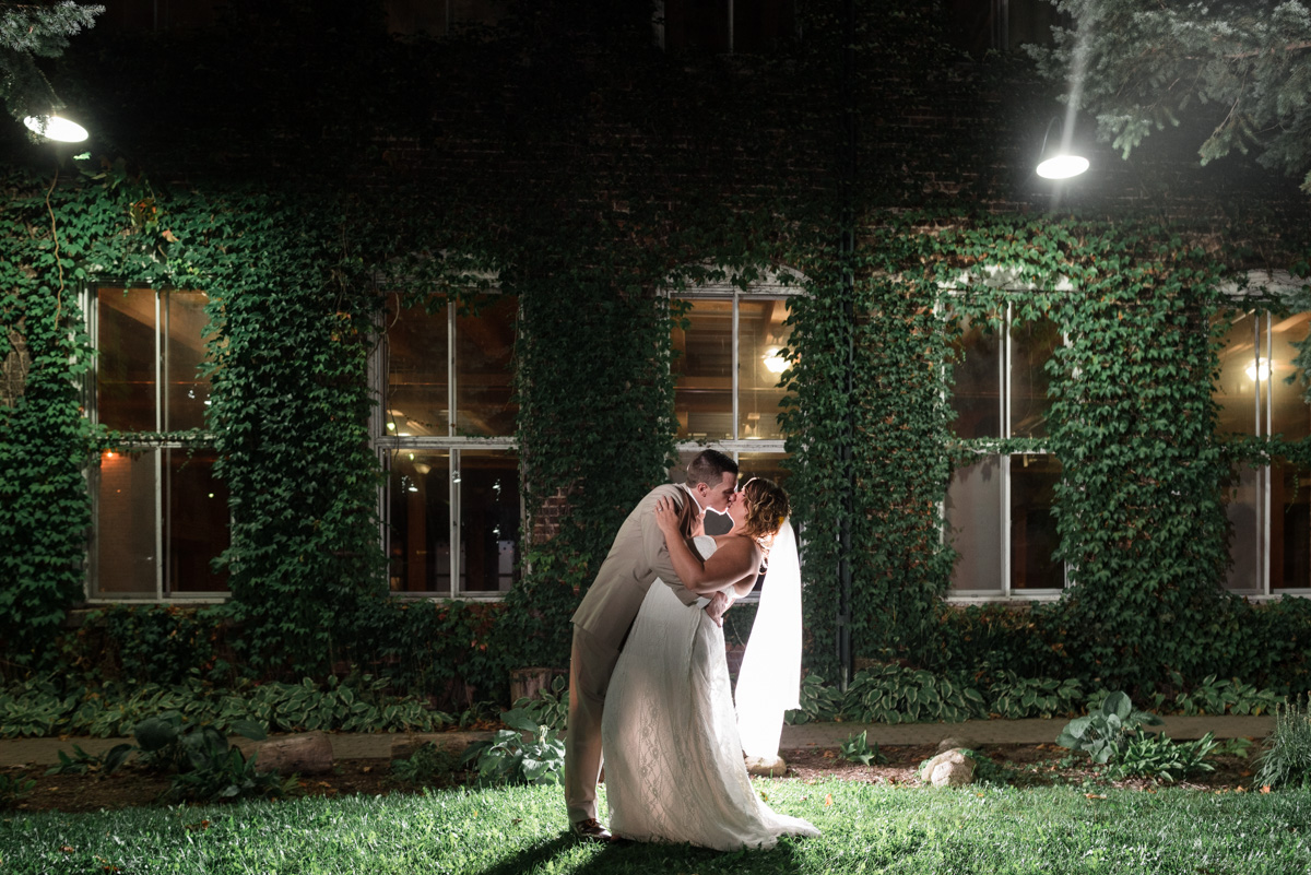 night photo outside starline factory.  groom dipping bride with backlighting