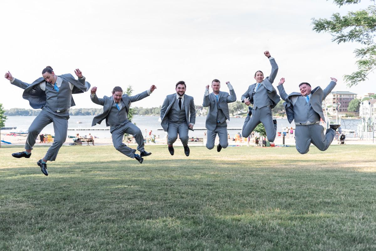Groom and groomsmen jump for joy on the banks of lake oconomowoc in wisconsin