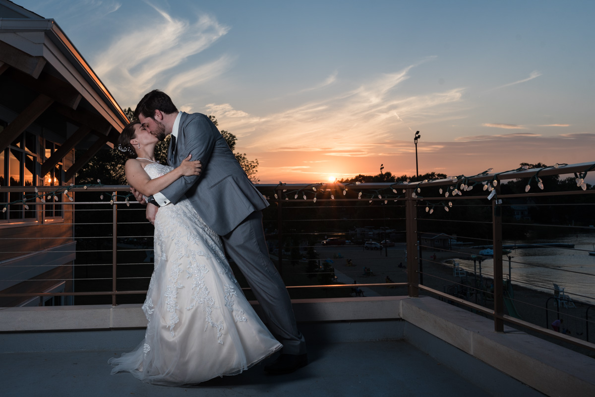 Bride and Groom kissing as sunsets behind them in oconomowoc, wisconsin