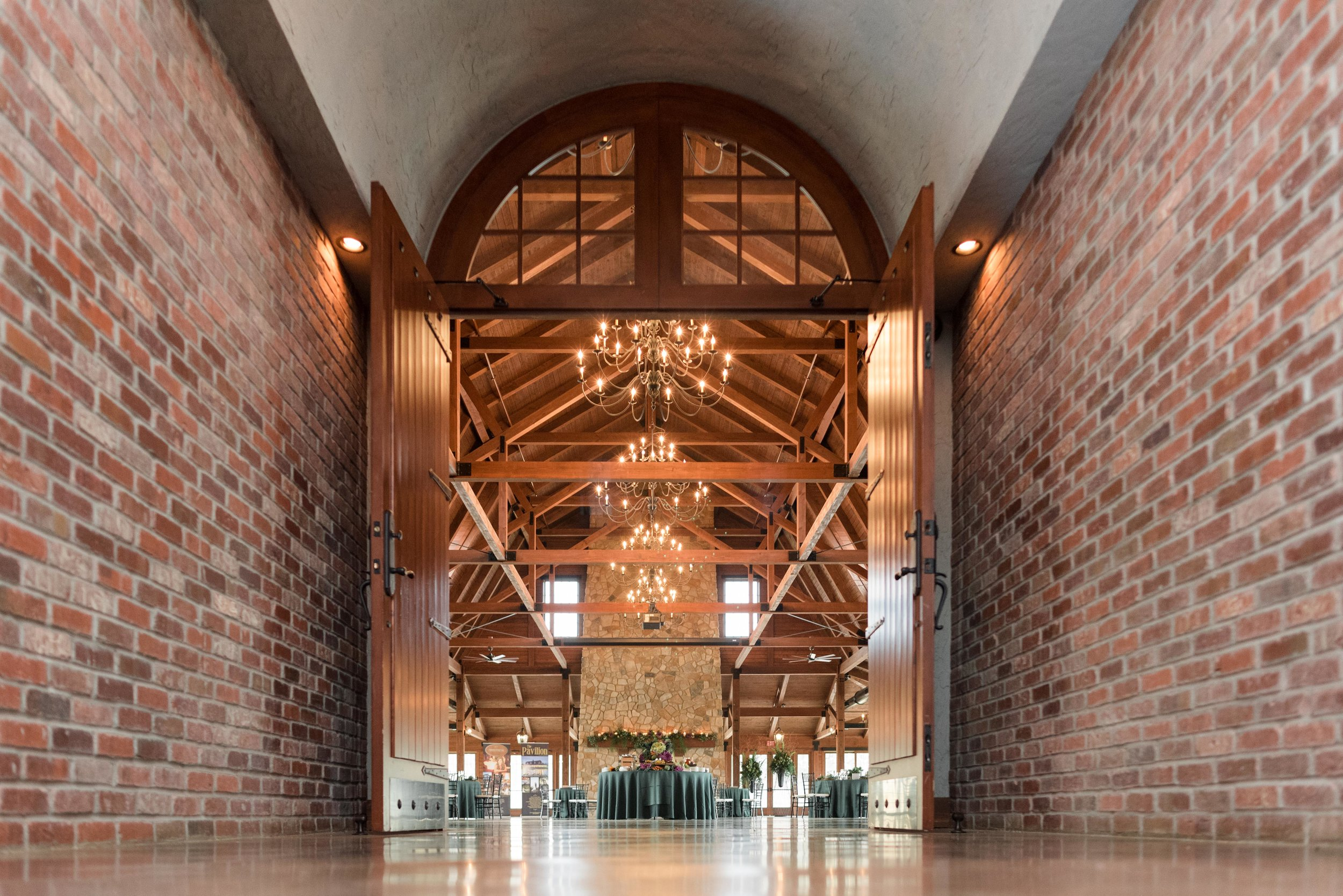Entrance into the Pavilion with brick walls and exposed beams above with floor to ceiling stone fireplace and chandeliers beautifully displayed with florals from Event Floral