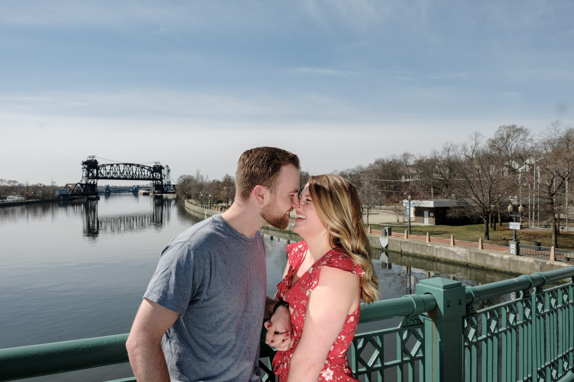 Couple kissing on bridge with beautiful blue sky above the river in Joliet, Illinois