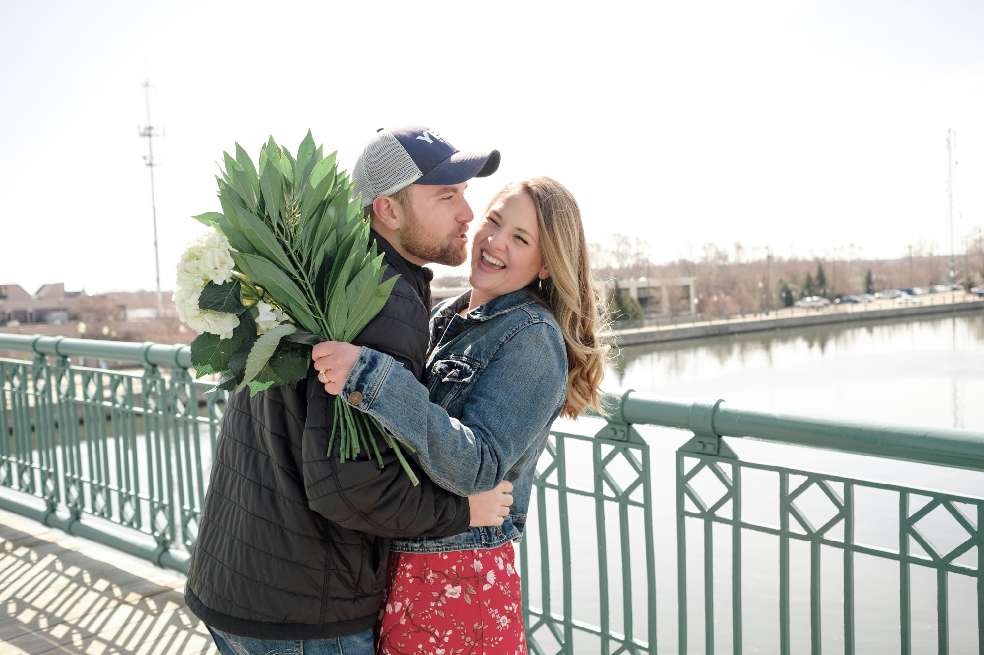 Couple laughing and kissing while holding flowers with water in background during engagement session in Joliet