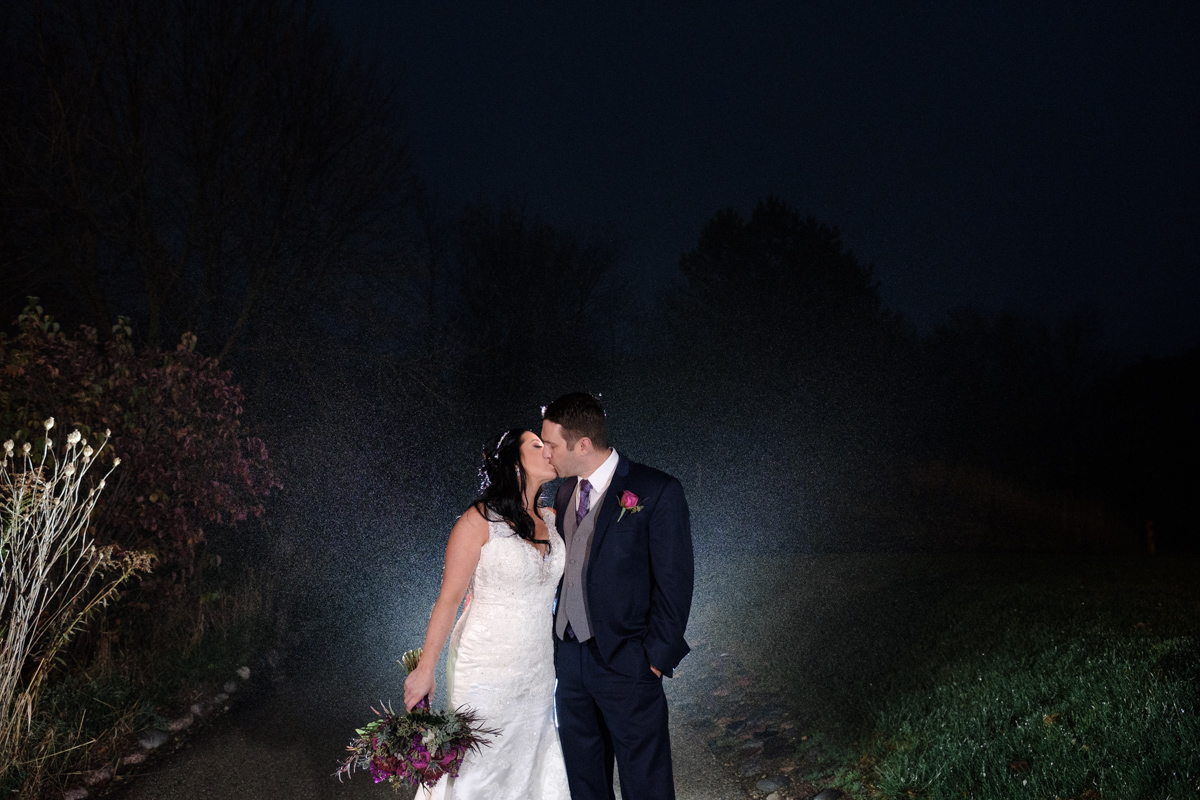 Lake Geneva Resort wedding with couple kissing after dark backlit with rain drops falling around them