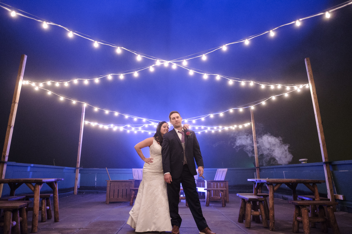 Couple standing under market lights with fog rolling in and blue lights illuminating the fog behind them after wedding at Lake Geneva Resort
