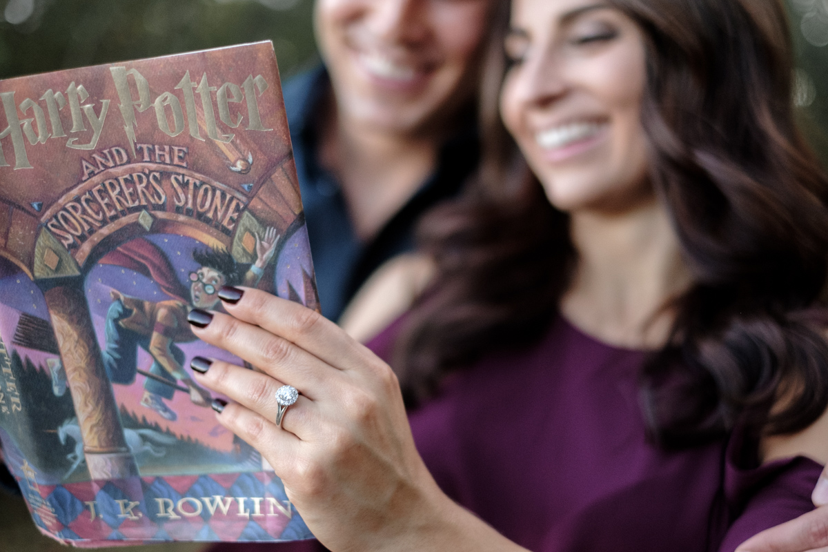 Couple reading Harry Potter during engagement session in rock cut state park