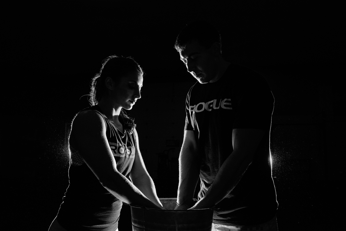 back lit photo of couple kissing and getting chalk for a lift at Crossfit Rockford